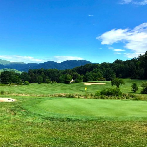 bright sunny day on a lush green golf course with the Plot Balsam Mountains in the background