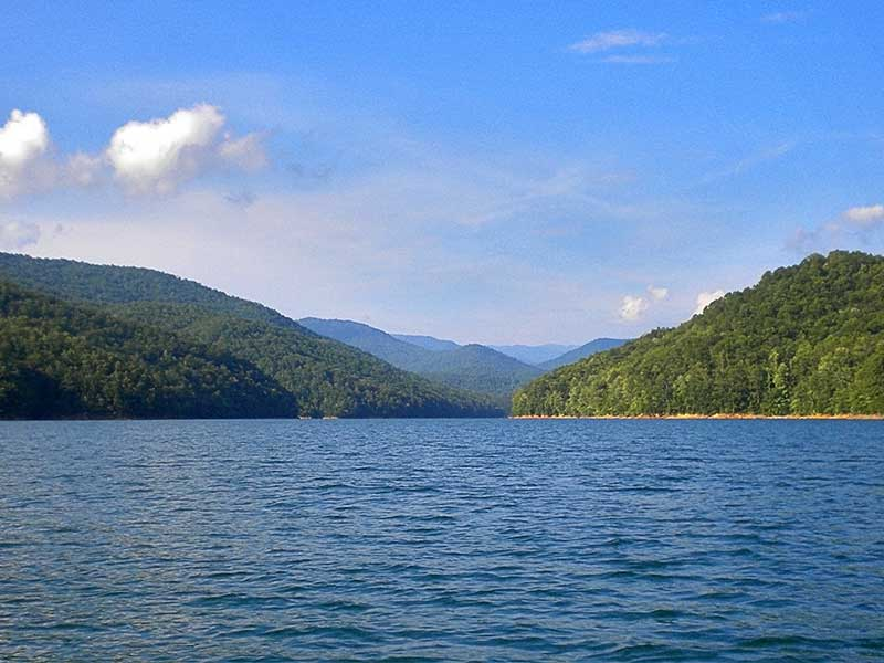 sunny day on Fontana Lake with clear waters and the Great Smoky Mountains in the background