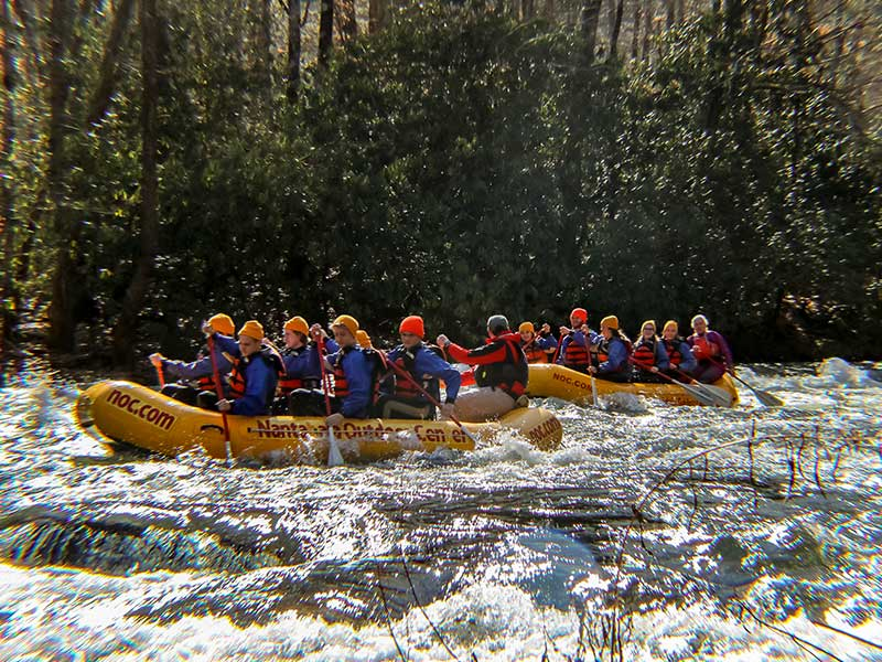 two groups of rafting guides for Nantahala Outdoor Center floating down Patton